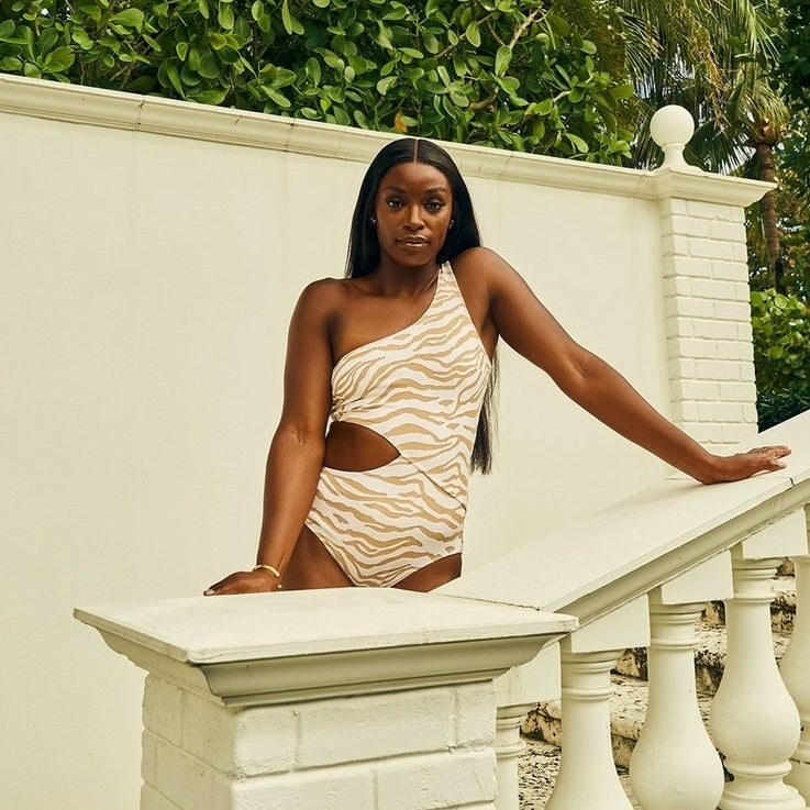 model wearing one-shoulder swimsuit with side cutout in whit with tan animal print
