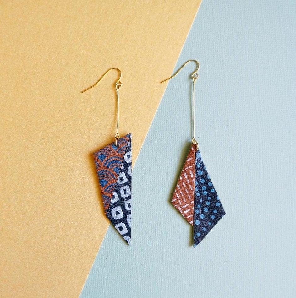 A pair of asymmetrical earrings against a funky backdrop