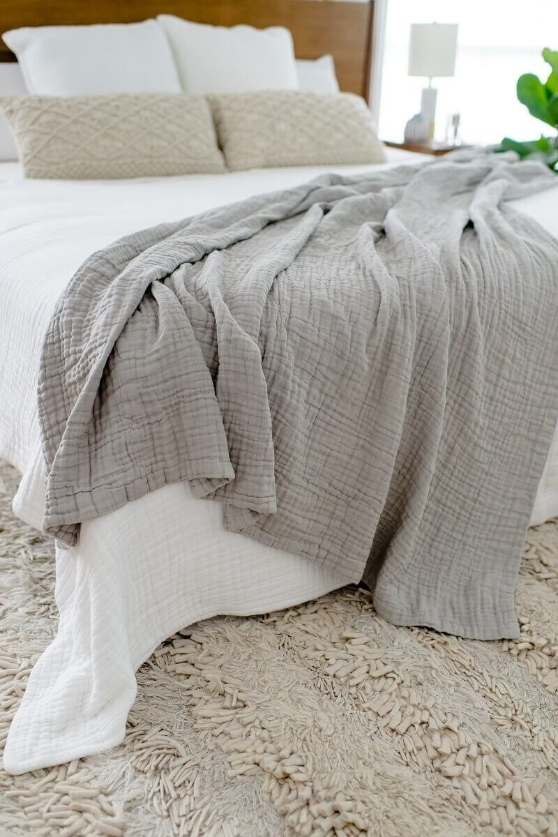 gray oversizes muslin comfort blanket on a bed that has a white comforter on it
