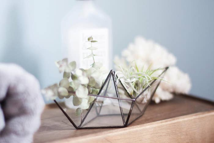 A glass origami boat on a desk with flowers in it
