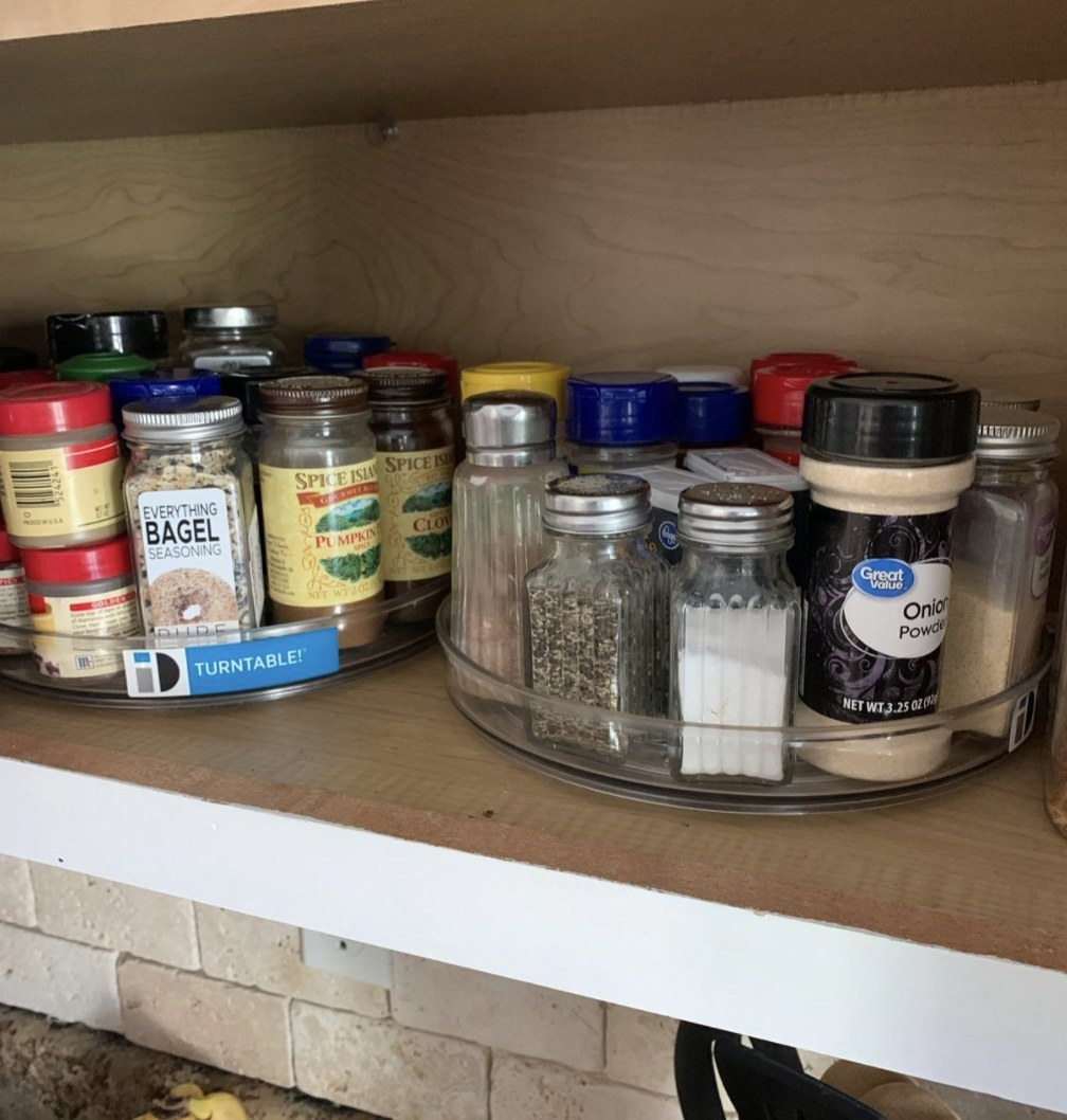 a reviewer's two lazy susan turntables holding spices in a cabinet