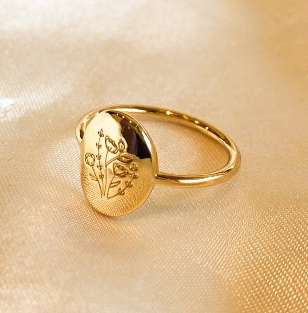 A shiny ring with wild flowers engraved on its face
