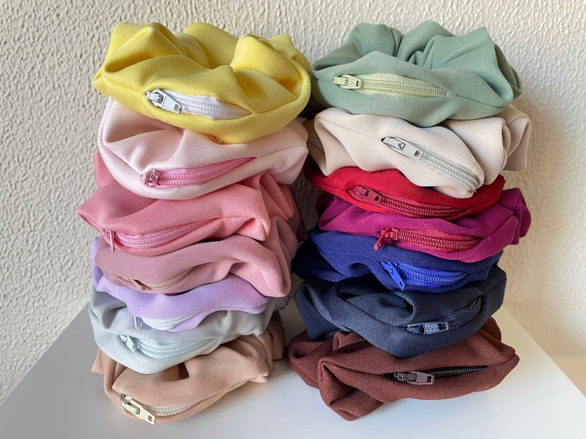 14 scrunchies of varying colours with zip-up pockets on each