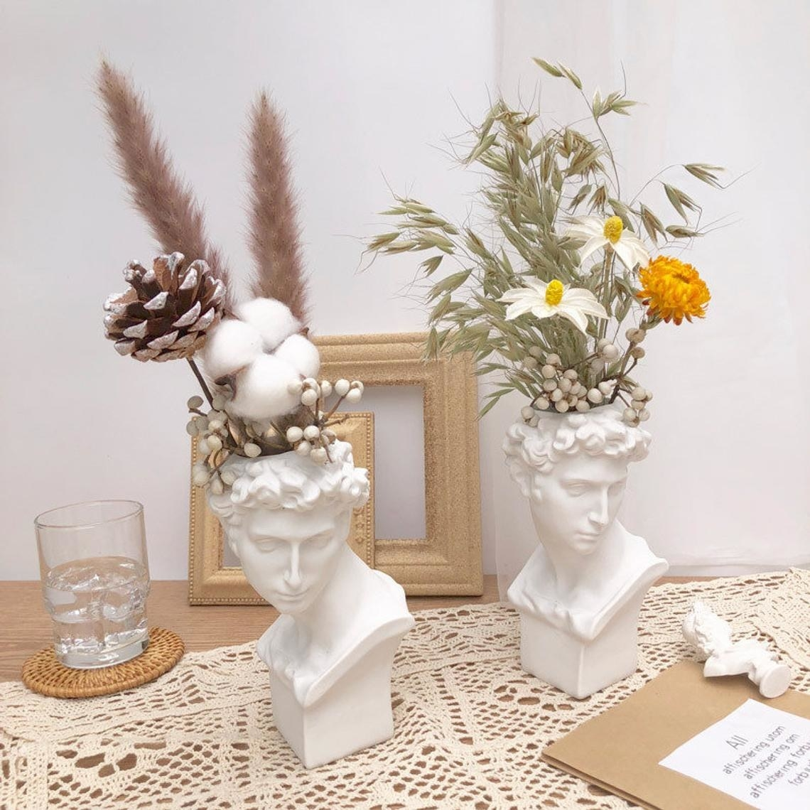 two bust vases on a table with flower arrangements in each