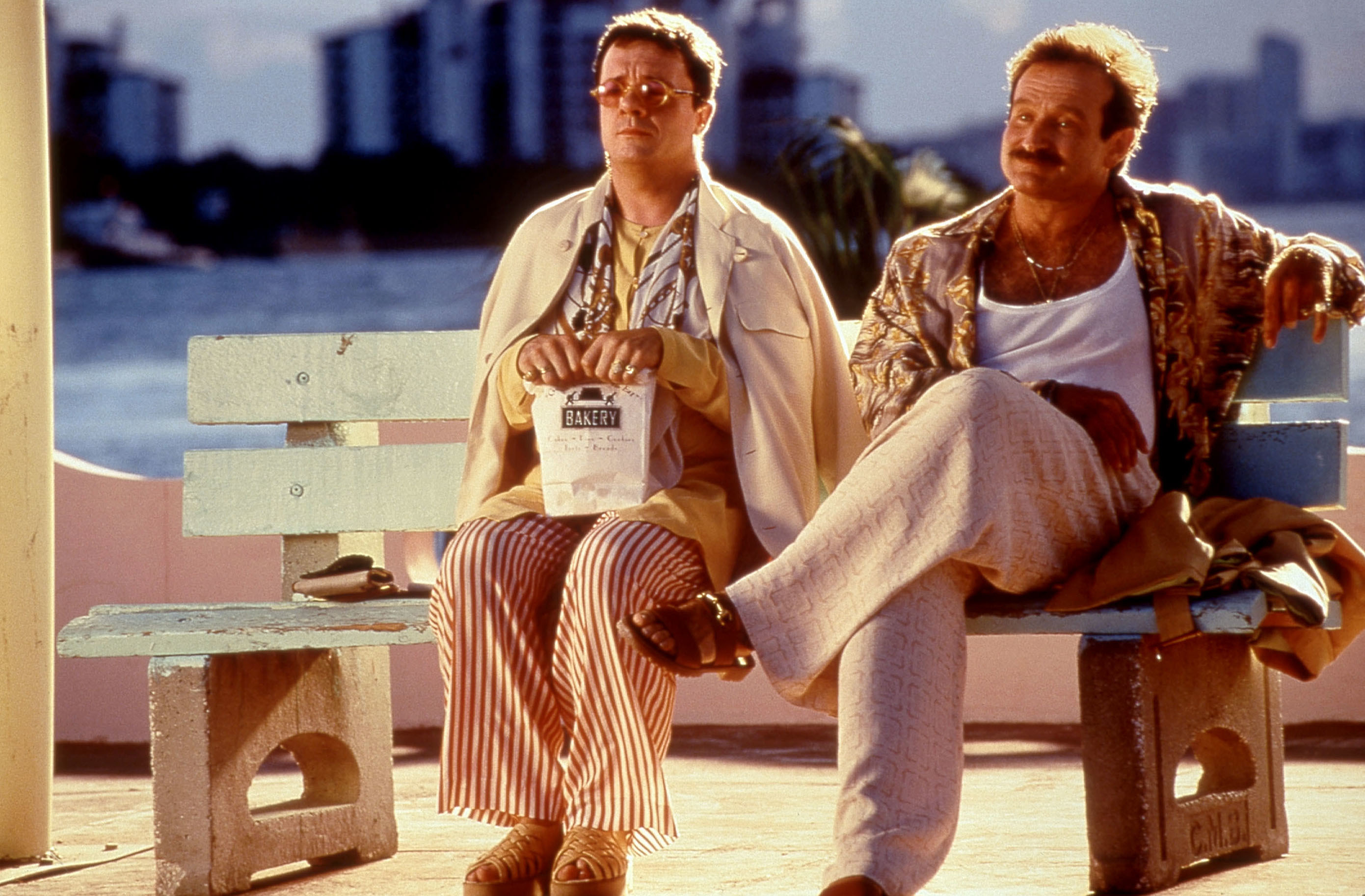 Nathan Lane and Robin Williams sit on a bench