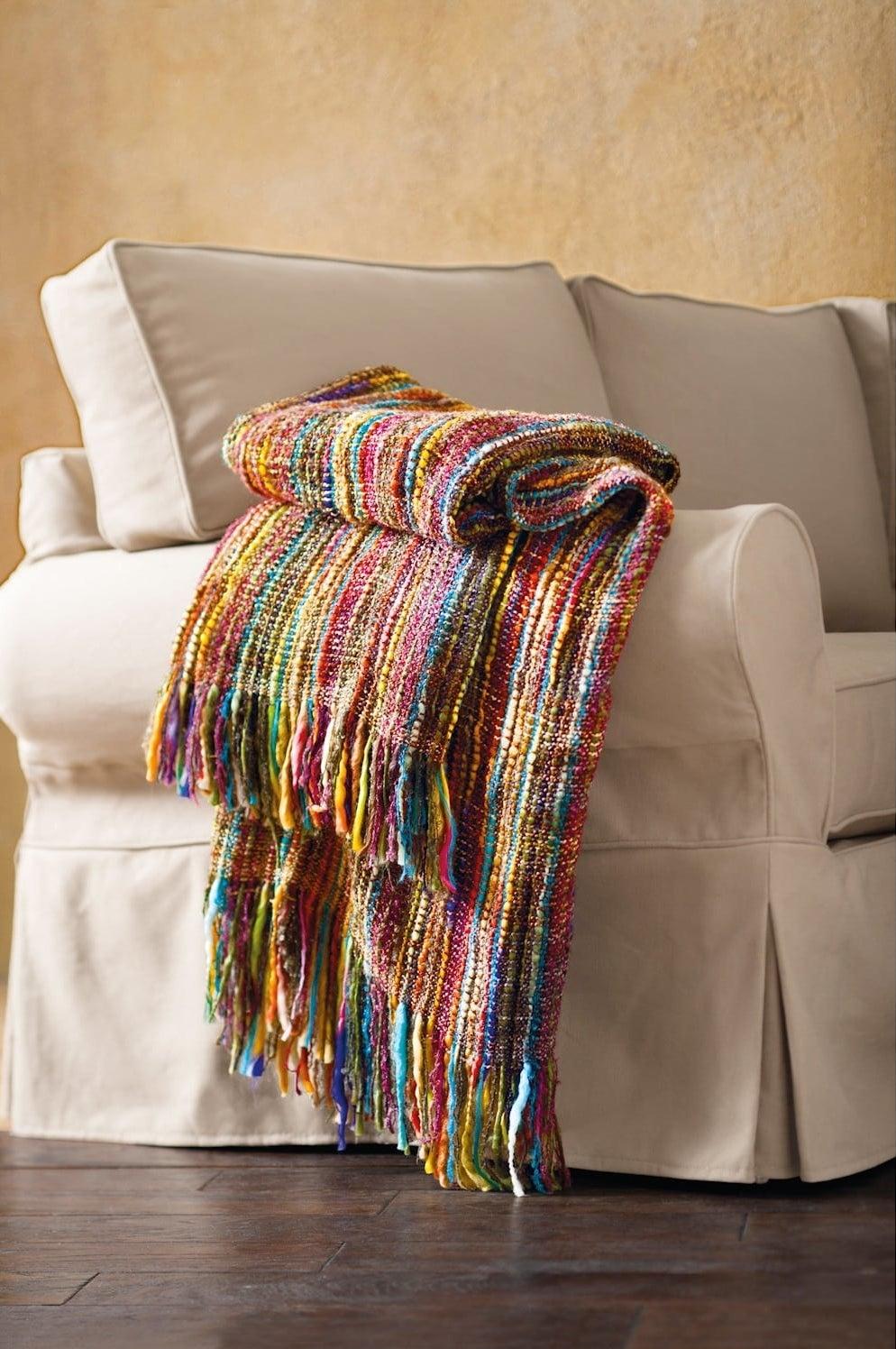 fringed rainbow throw on a couch
