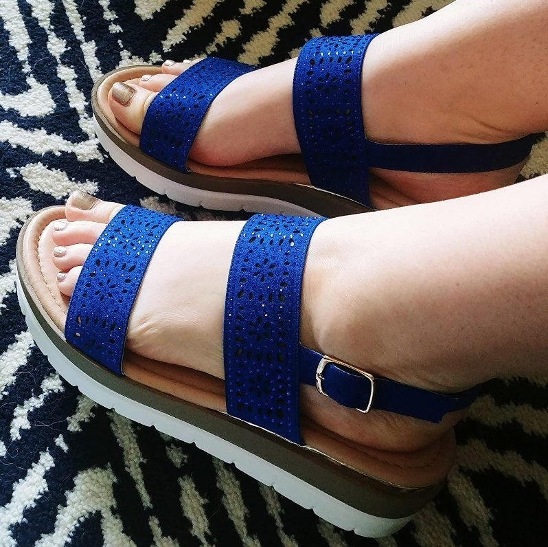 A reviewer wearing royal blue sandals with laser cut details