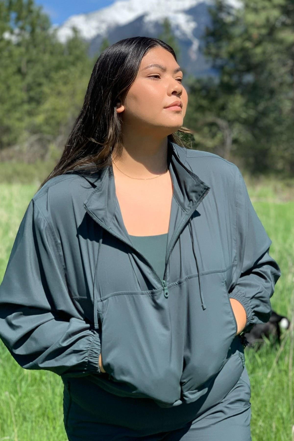 a model in a green half zip wind breaker
