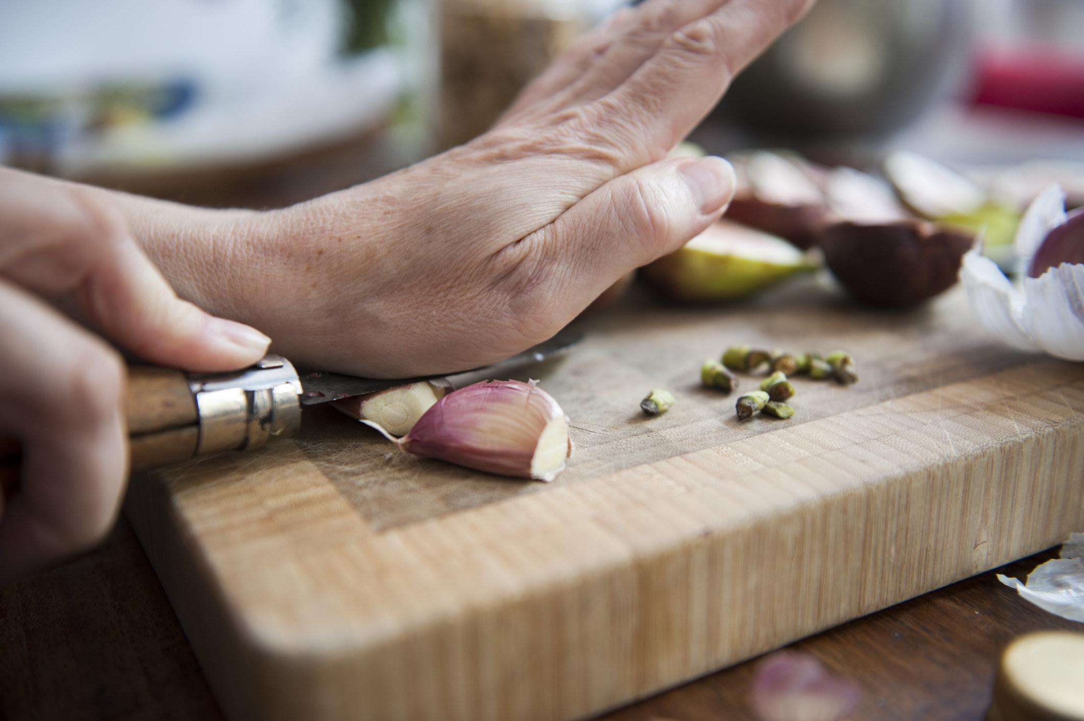 Someone peeling garlic on a cutting board