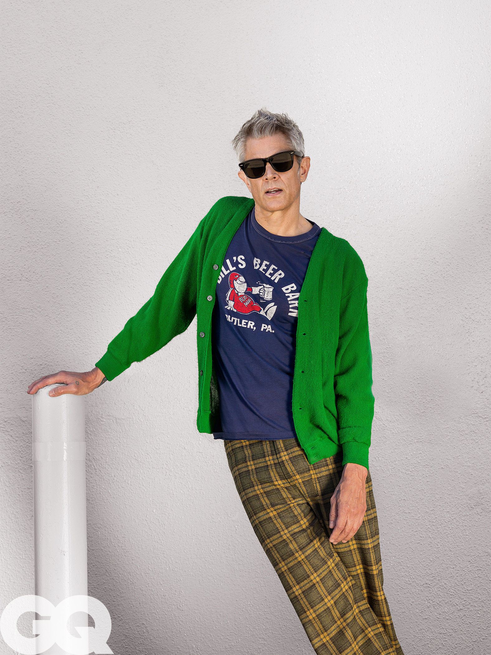 50-year-old Johnny posing for GQ in a T, cardigan, and plaid pants