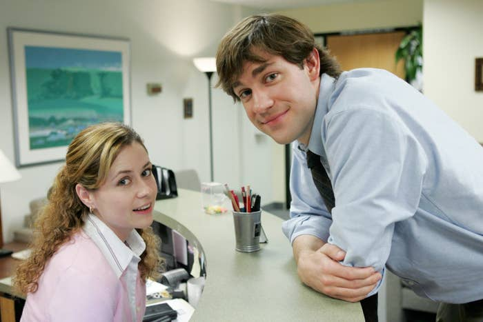 Pam smiles while Jim leans over on her desk