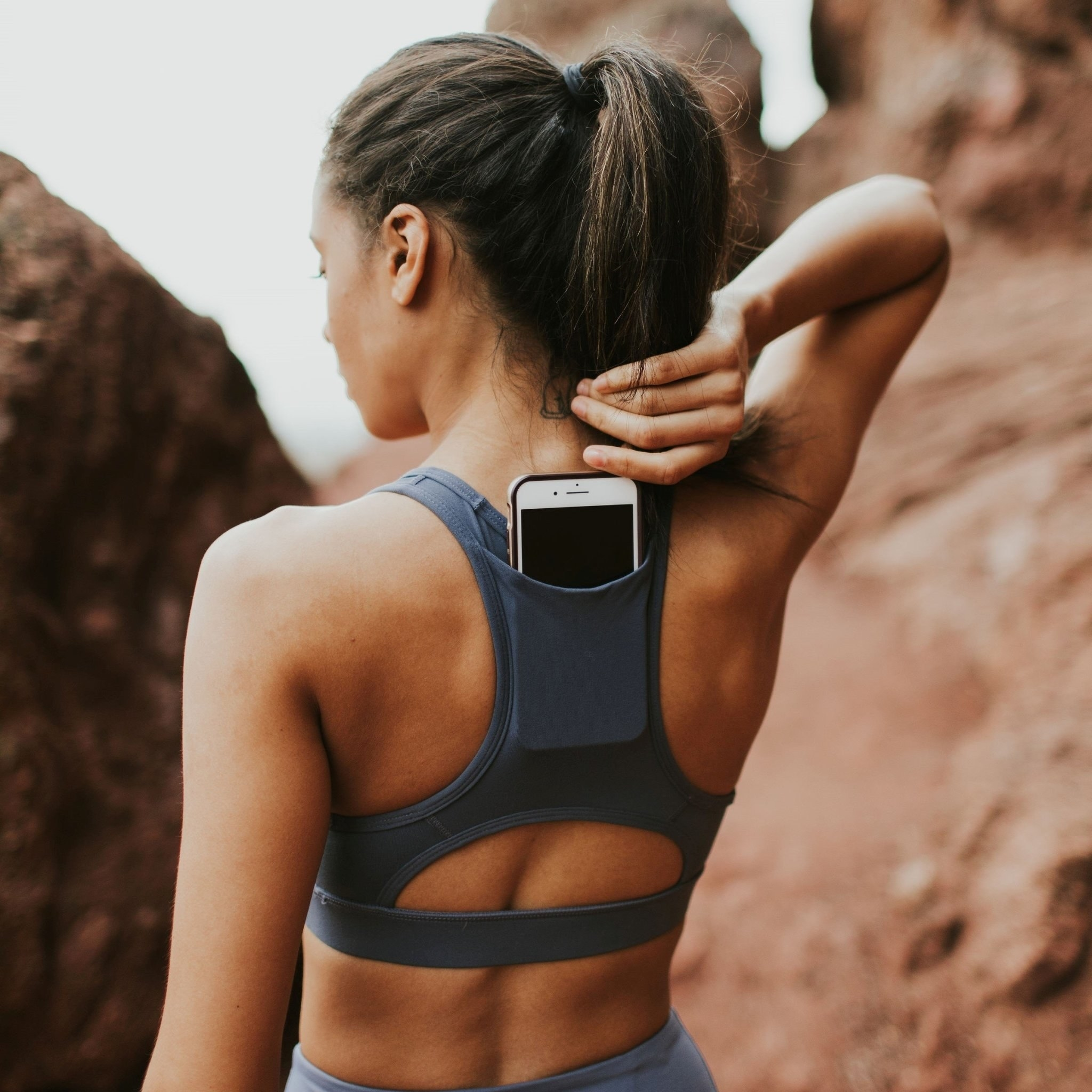 a model reaches for the phone in the pocket on the back of the navy sarah sports bra