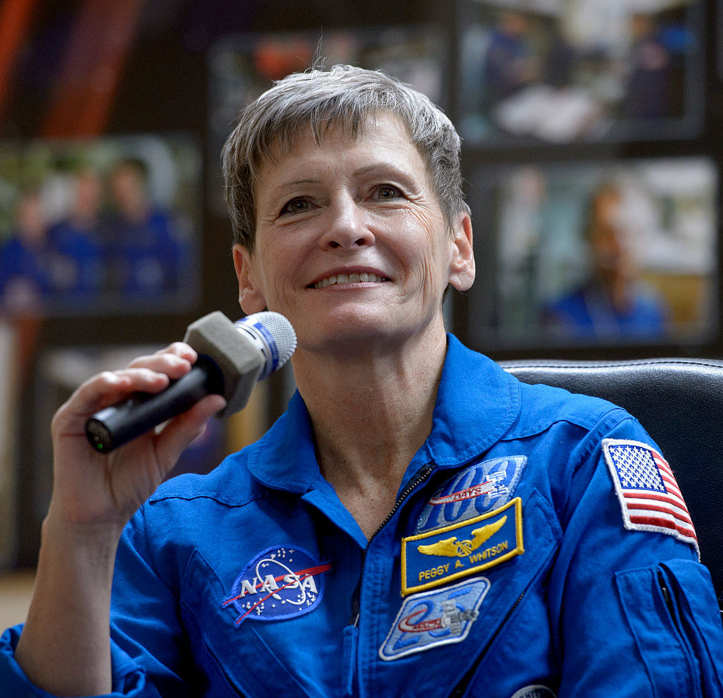 Peggy Whitson holding a microphone in her NASA jumpsuit