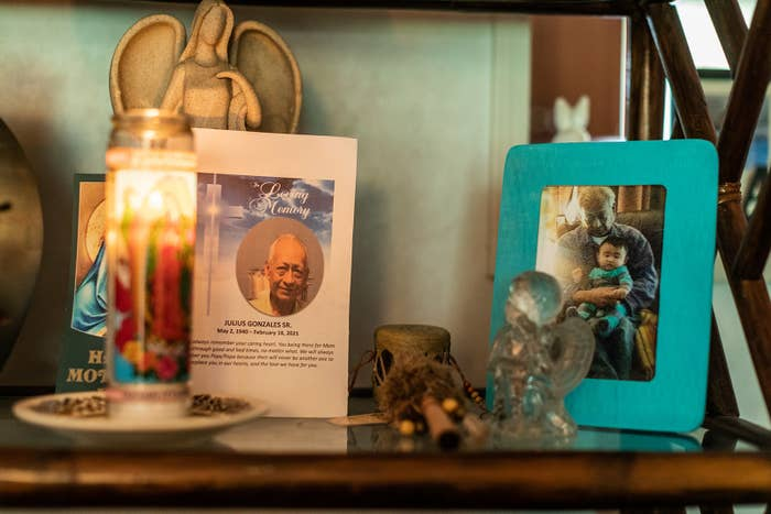 A shelf shows a small ceramic angel statue, a funeral program for Julius Gonzales Sr, a Lady of Guadalupe candle, and a picture of an older man holding an infant in his lap