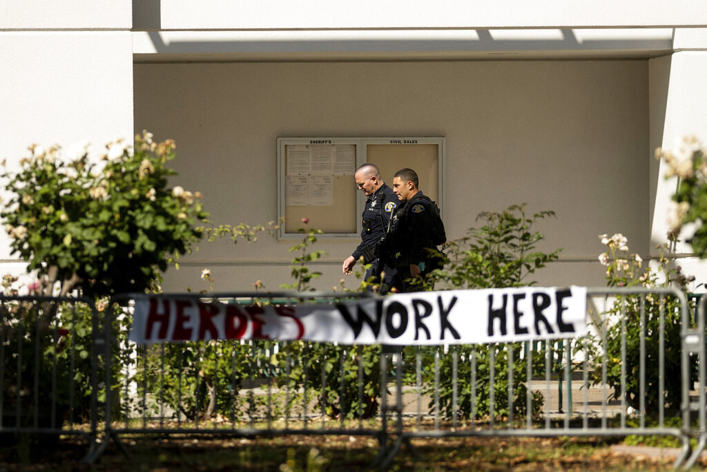 """Two police officers walk behind a fence where a sign reading """"Heroes work here"""" is posted"""