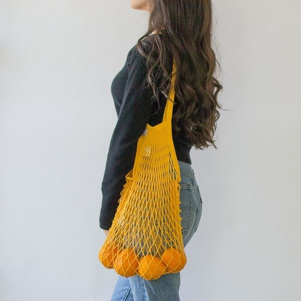 someone wearing the net bag with oranges inside and the color of the bag is mustard yellow