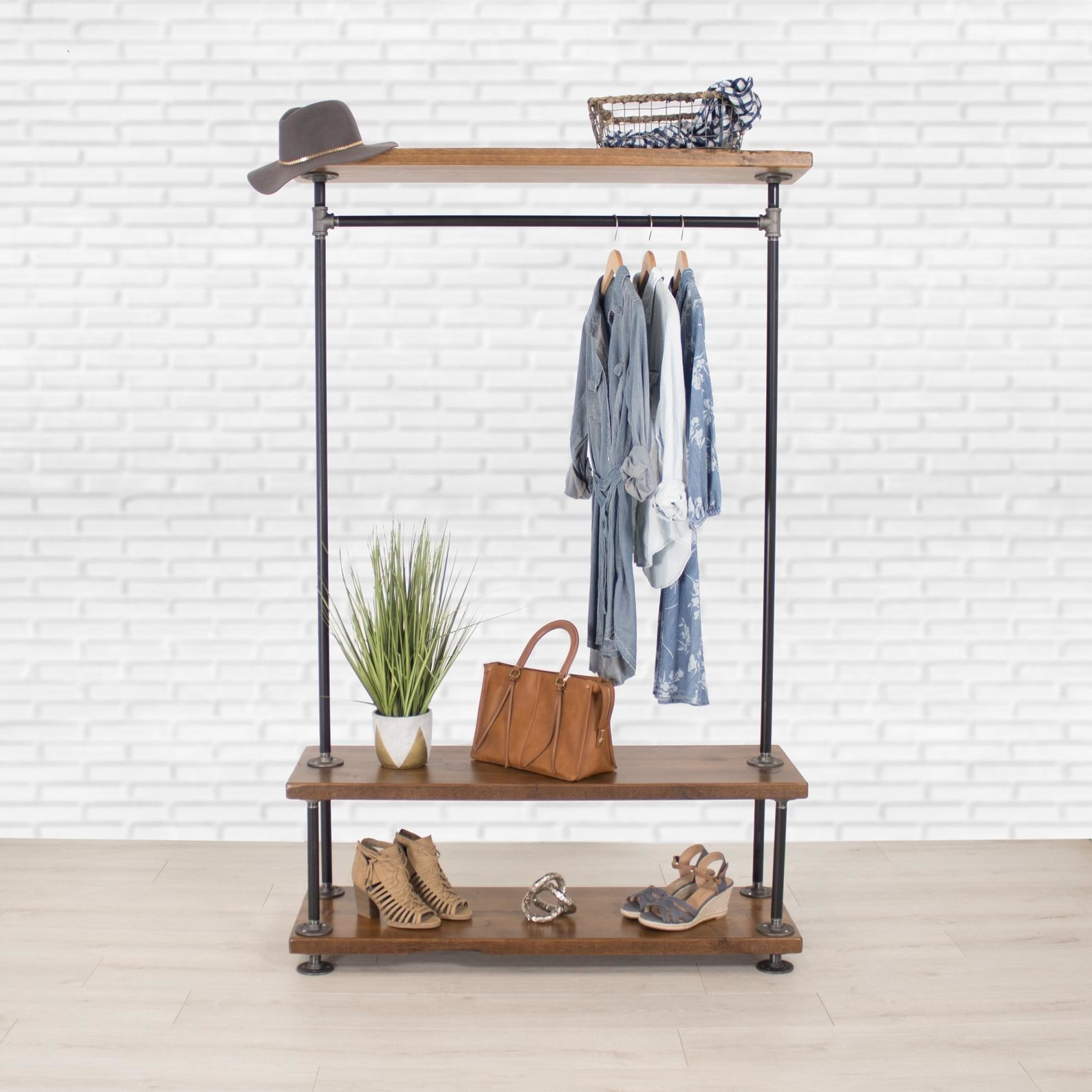 metal clothing rack with two wood shelves on the bottom and one on the top