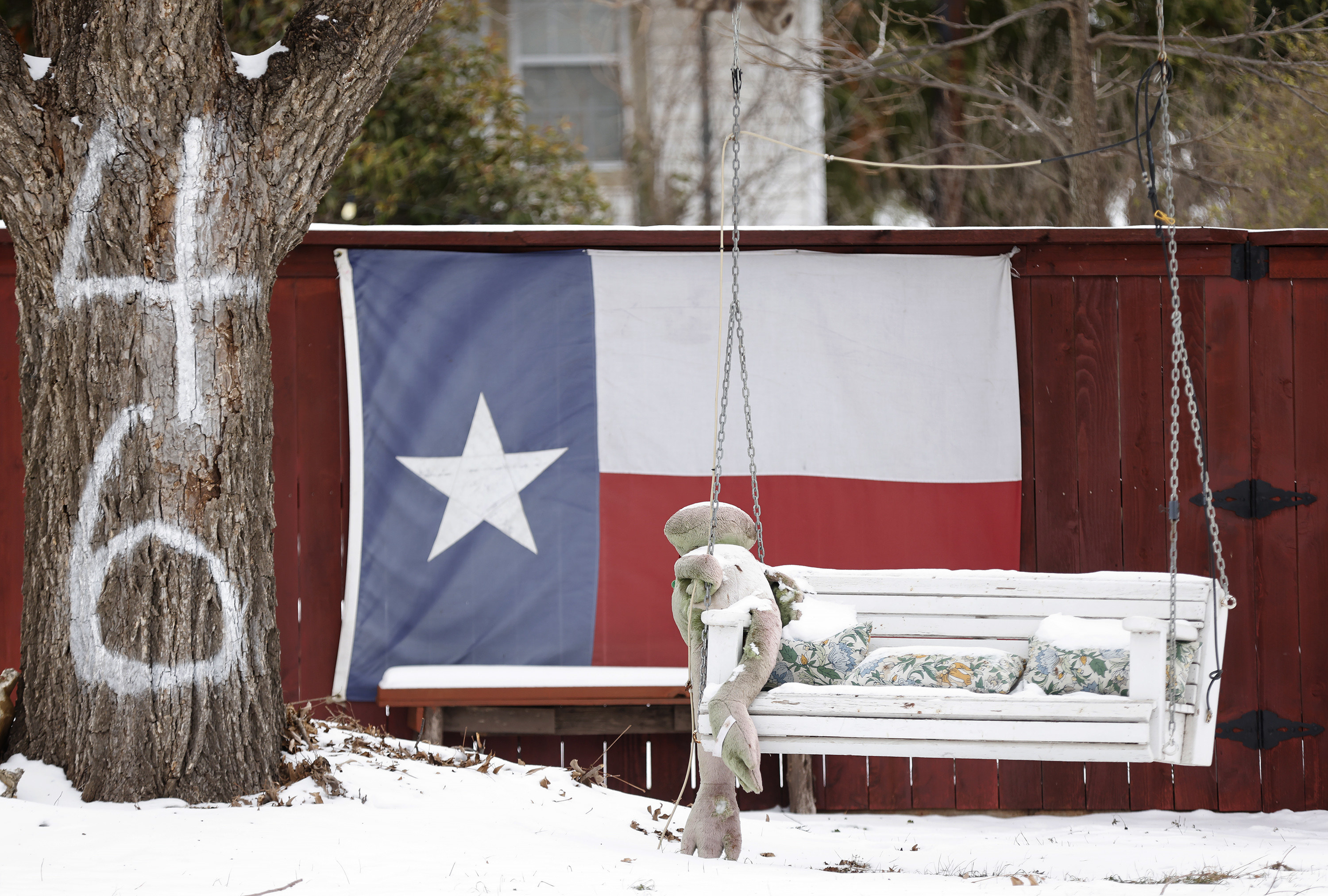 The Texas flag hangs on a fence by a snow-covered bench