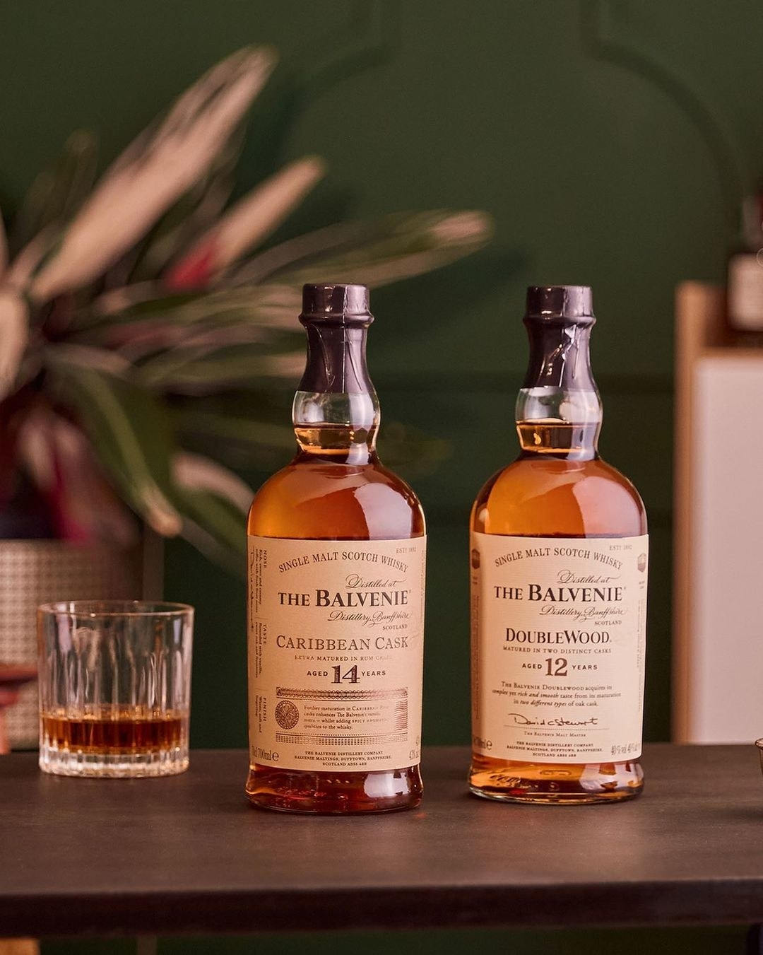 two bottles of Balvenie whiskey with a glass of whiskey in the background