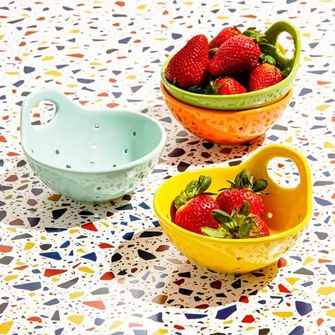 a set of four colorful colanders