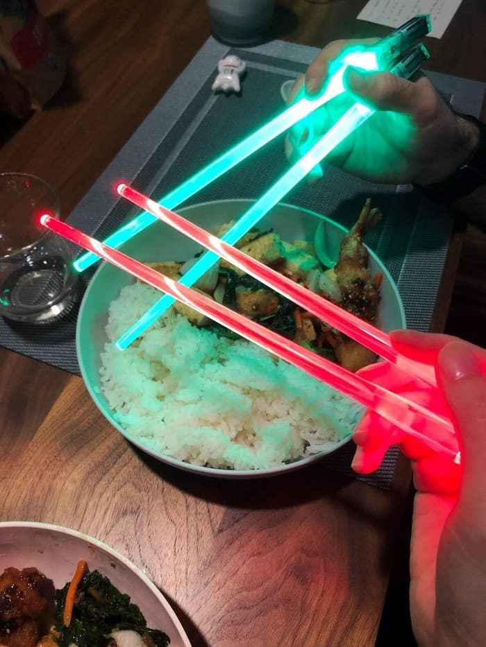 Reviewers holding light-up lightsaber chopsticks