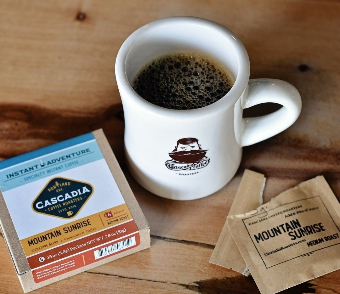 a mug filled with coffee next to a small box and an open packet of the Mountain sunrise coffee mix