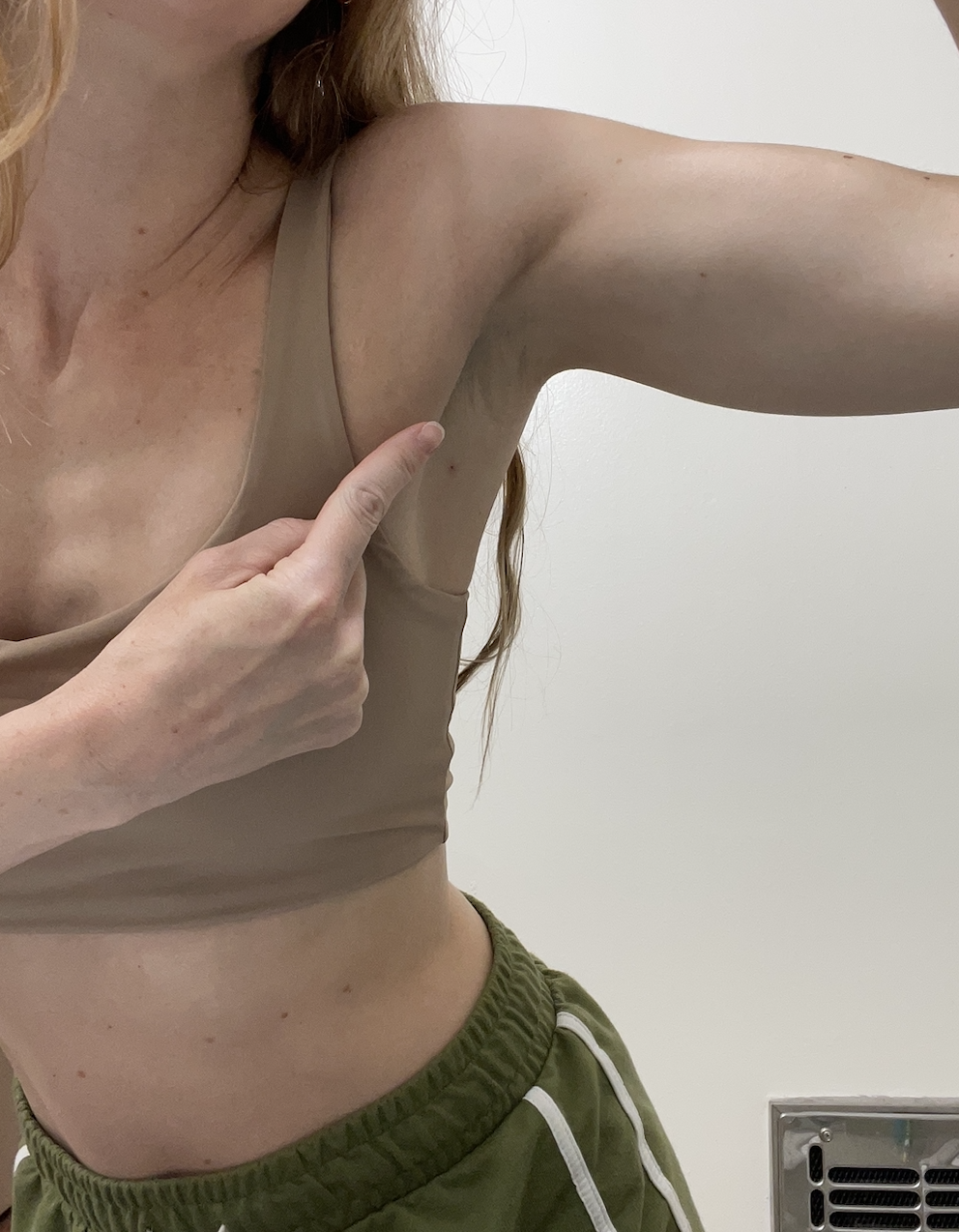 一个女人指着她隆起的腋窝