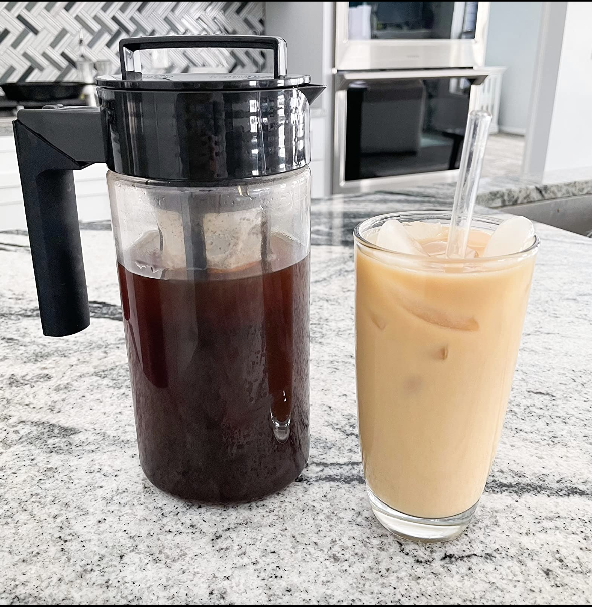 A pitcher of cold brew coffee next to a cup of creamed cold brew