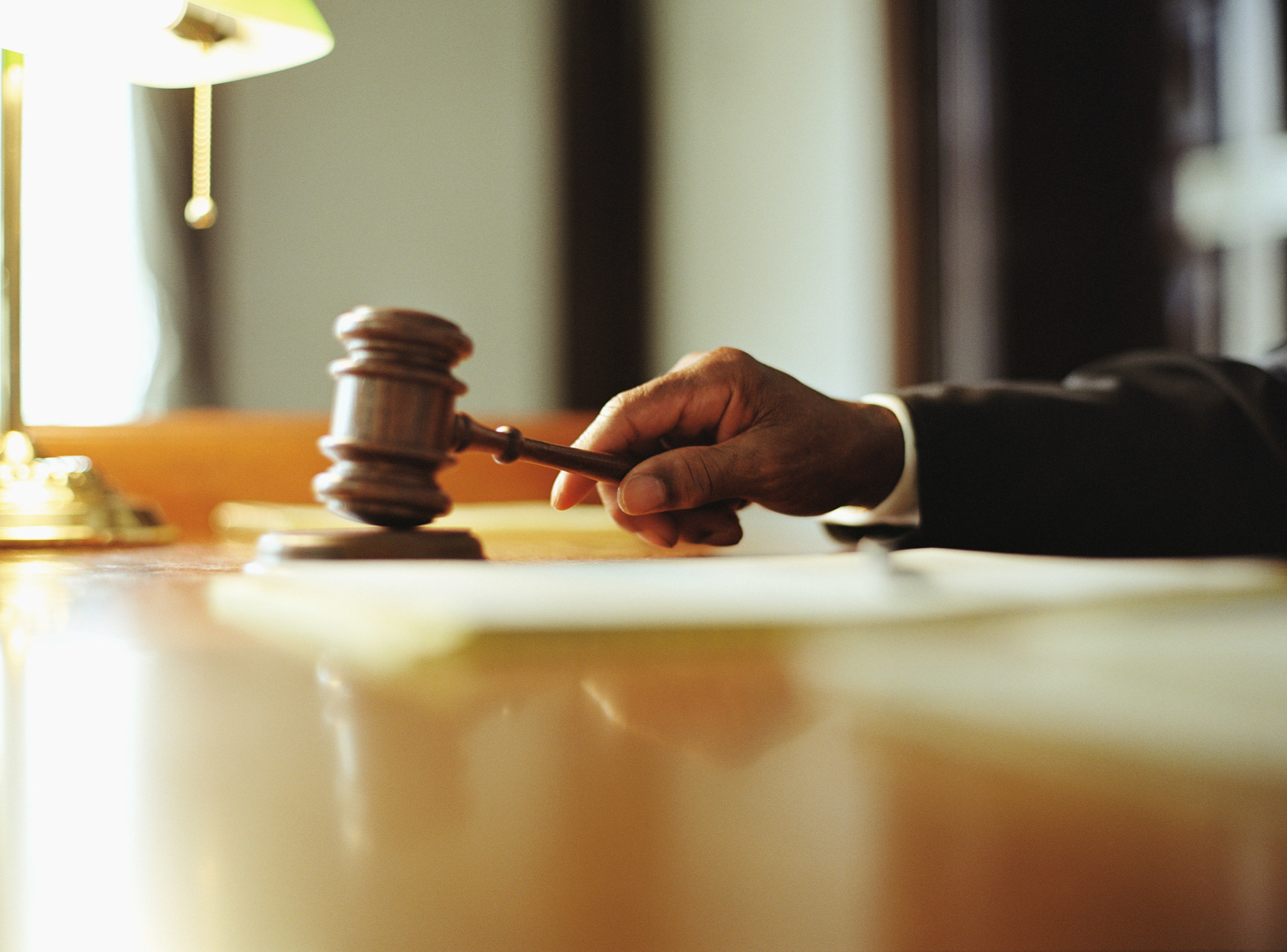 A judge's hand holding a gavel