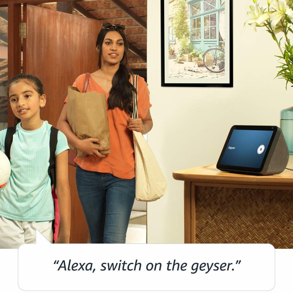 Two people entering their home, commanding the device to switch on the geyser.