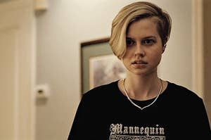 Siobhan with short hair shaved on one side, wearing a t-shirt, looking concerned