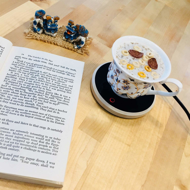 Mug kept on the device beside an open book on a desk.