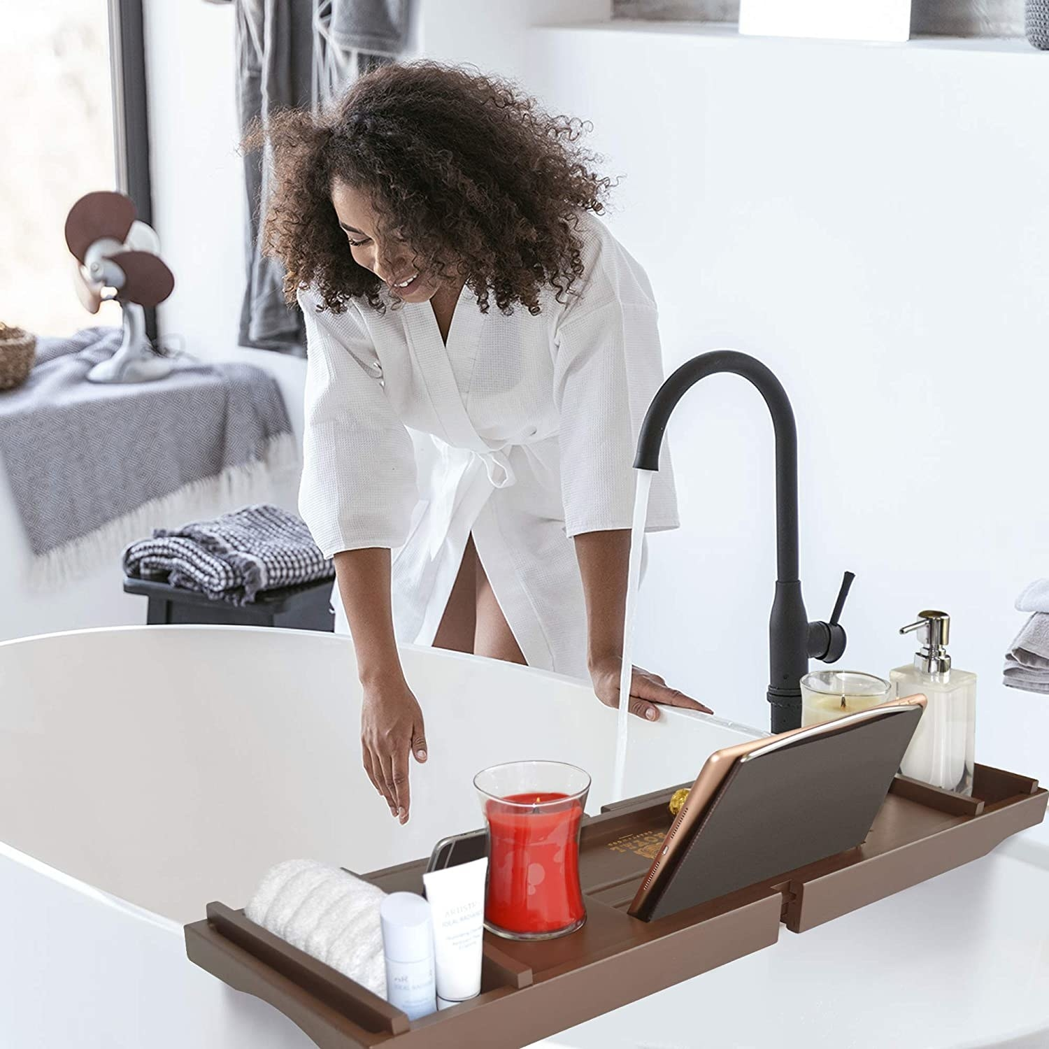 Bath caddy set up over a bathtub and a person standing beside it in a bathrobe.
