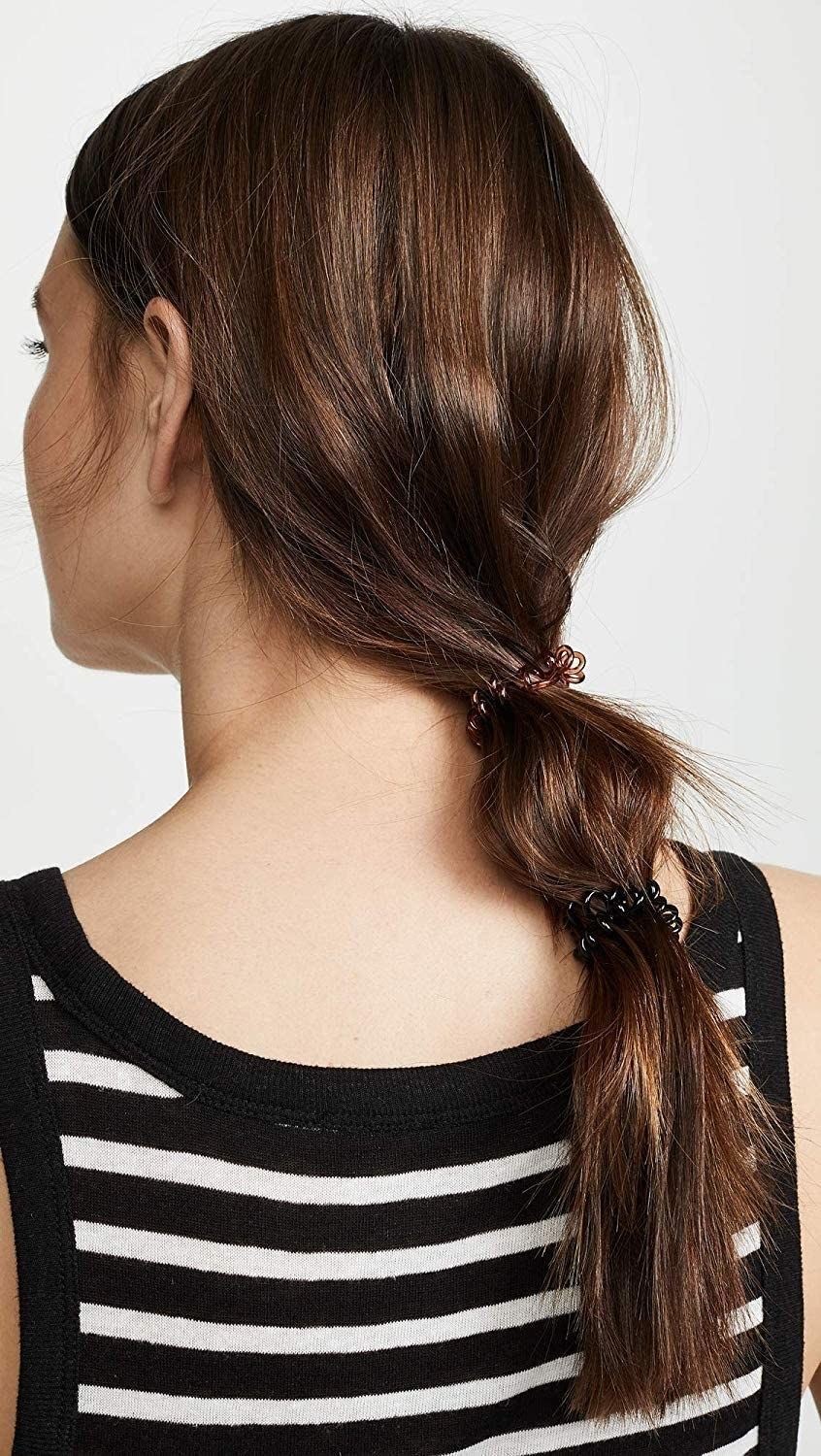 A person with their long hair in a ponytail using coiled hair ties