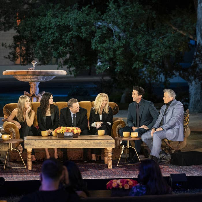 The Friends cast sitting and laughing on the reunion set