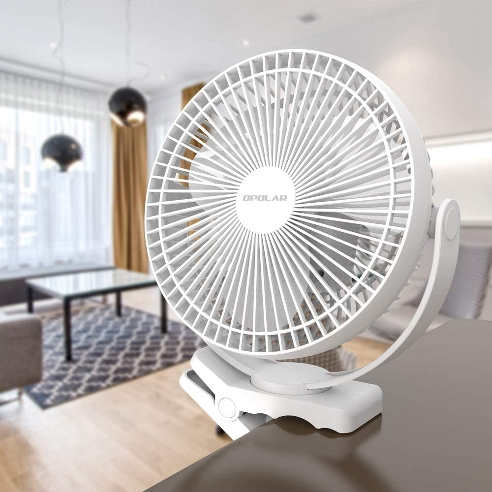 The fan clipped to a table in a living room