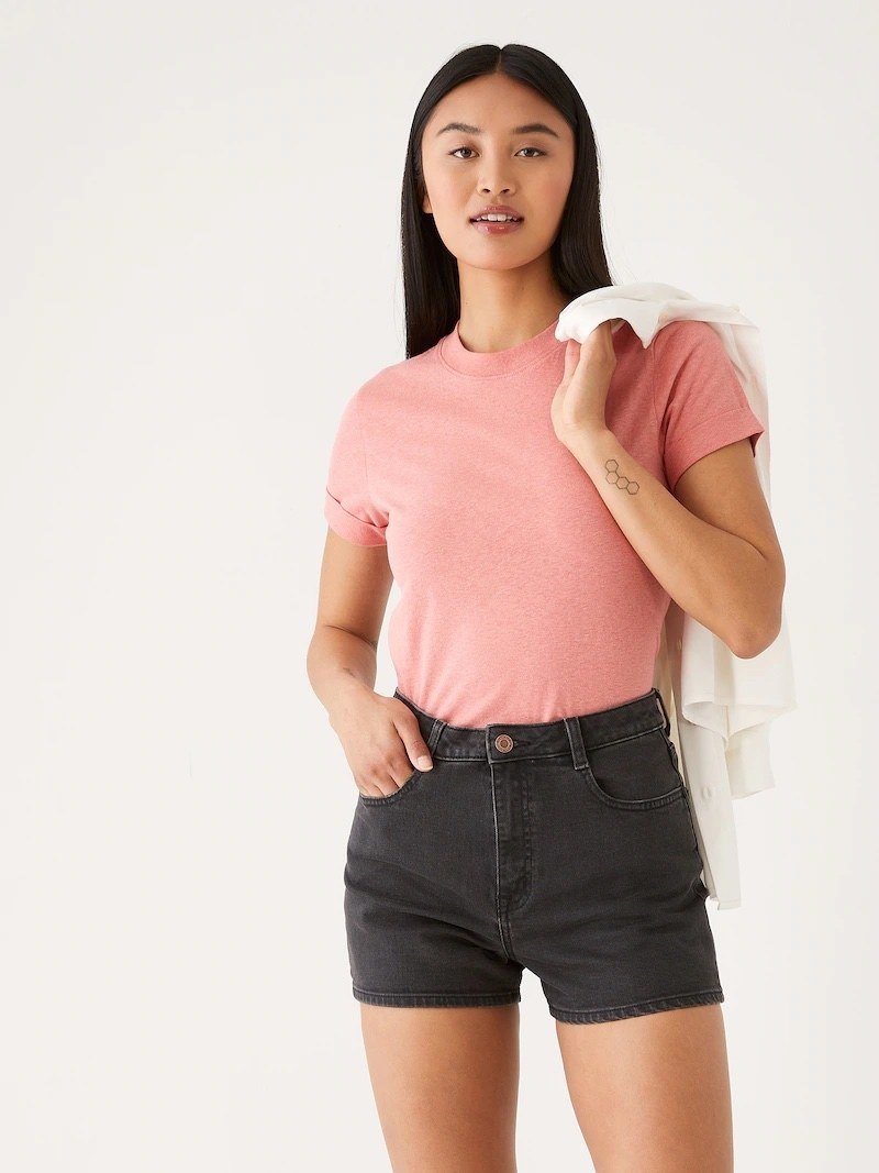 a model wearing the black shorts and a pink tee