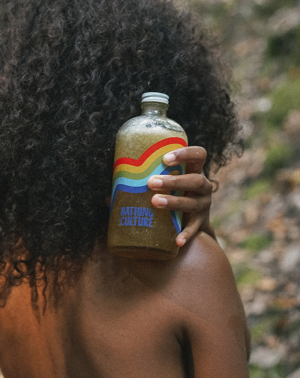model holding a glass bottle of body wash with a rainbow design on the front