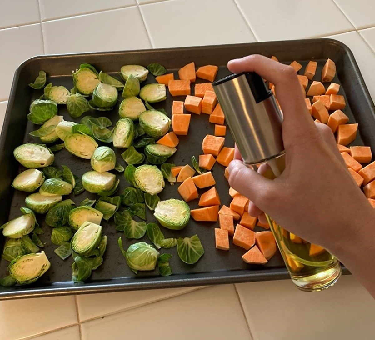 reviewer spraying veggies with olive oil using the spray bottle