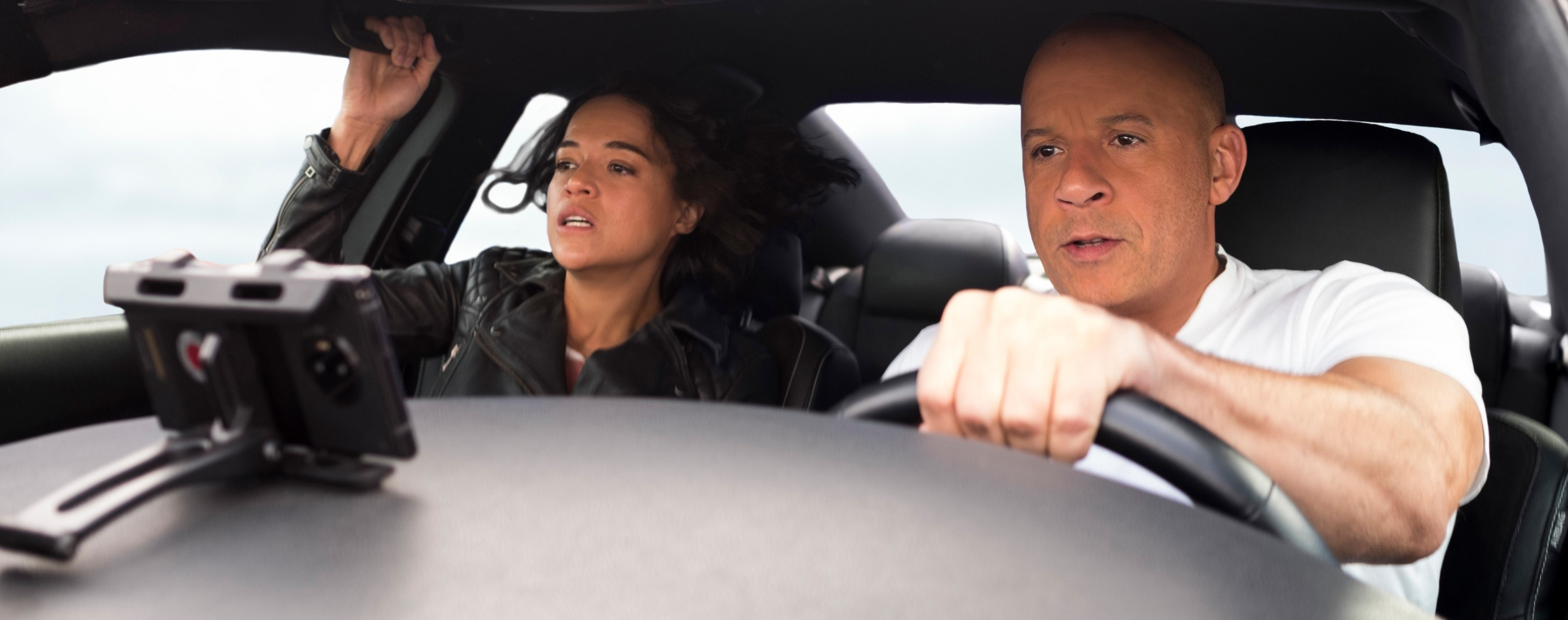 from left is Michelle Rodriguez and on the right Vin Diesel driving in a car for the movie fast and furious 9
