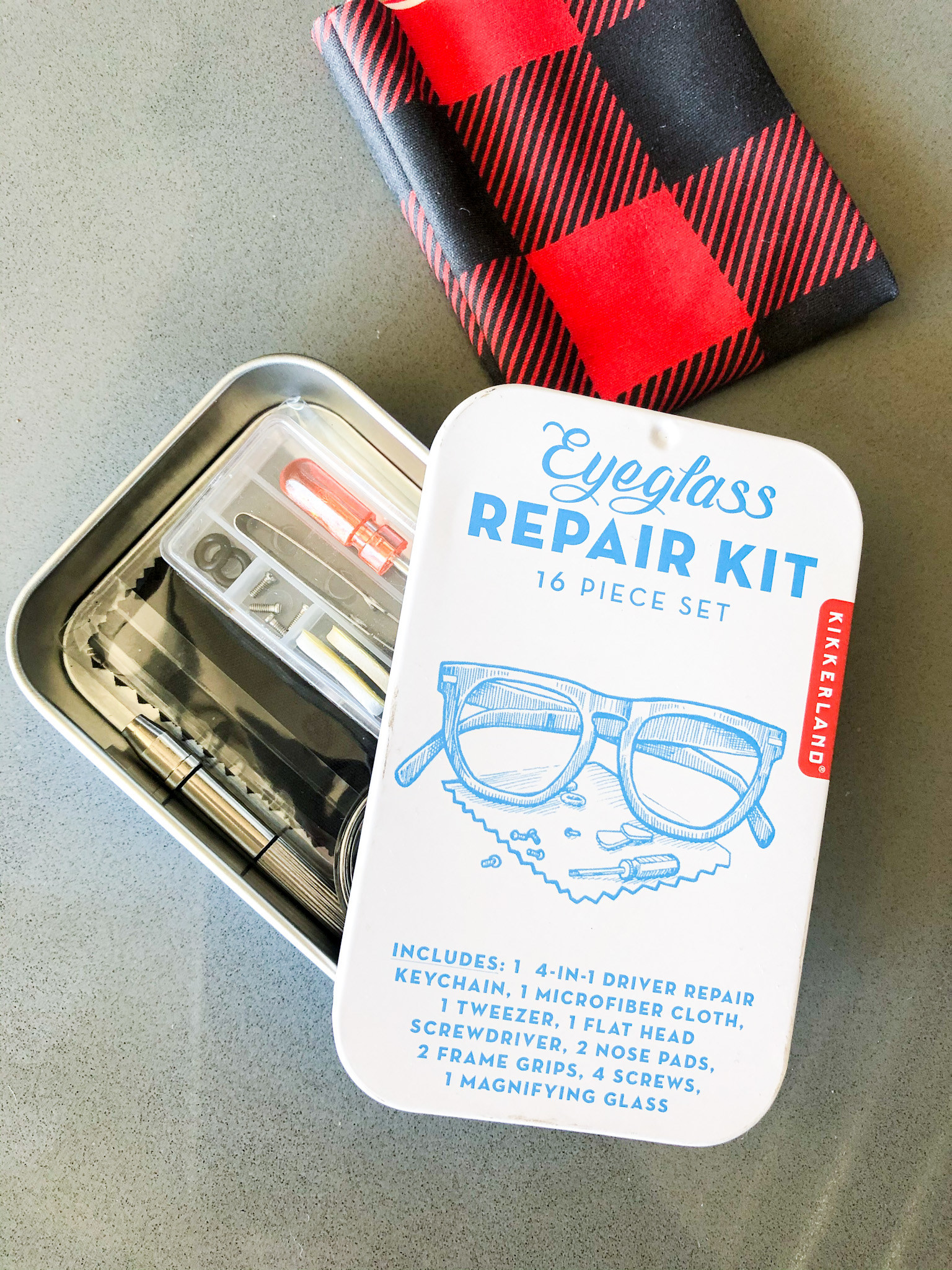 A flatlay of the open eyeglass repair kit showing what's inside