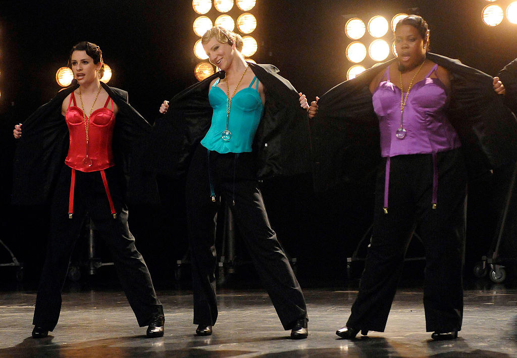 Lea, Heather, and Riley performing on stage in a scene from Glee