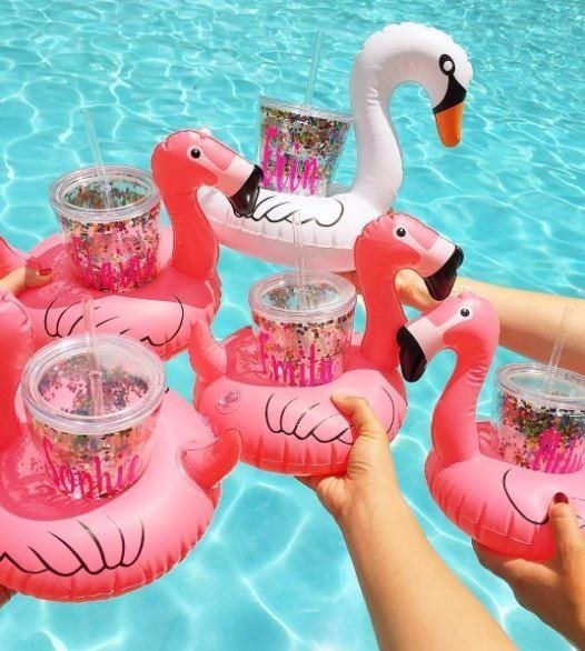 A group of reviewers poses with pink flamingo drink floaters in a pool