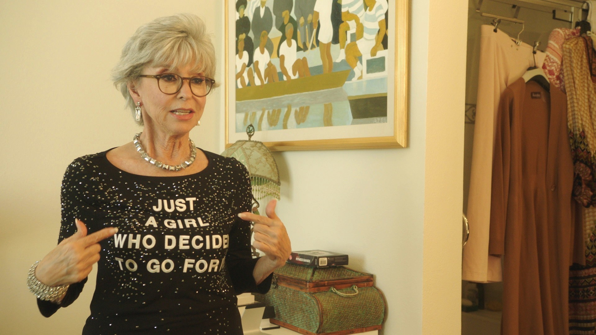 """Rita  Moreno pointing to herself and her shirt titled """"Just a girl who decided to go for it"""""""