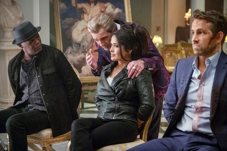 Ryan Reynolds, Samuel L. Jackson and Salma Hayek sitting while being integrated by  Antonio Banderas