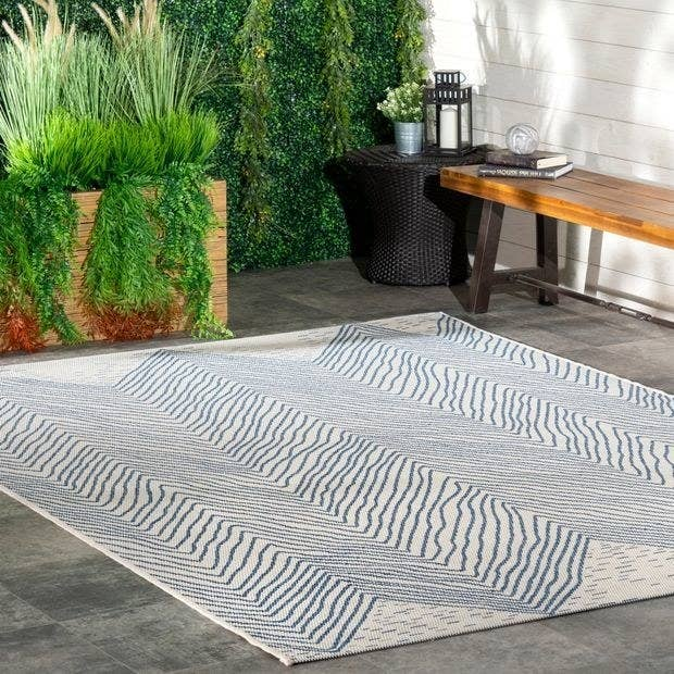 rectangle blue and white chevron-printed rug on small patio