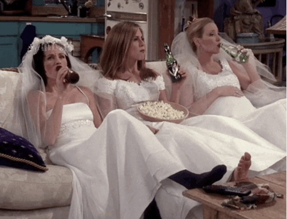 Monica, Rachel, and Phoebe all wearing wedding dresses and kicking back on the couch