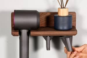 organizer holding a Dyson dryer, an incense burner on top, and two attachments on the bottom