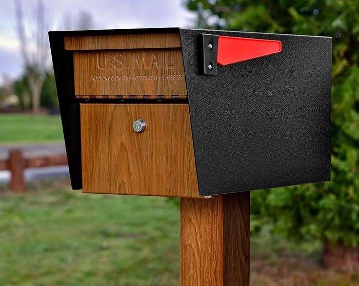 a wood and metal mailbox mounted on a post with a red flag
