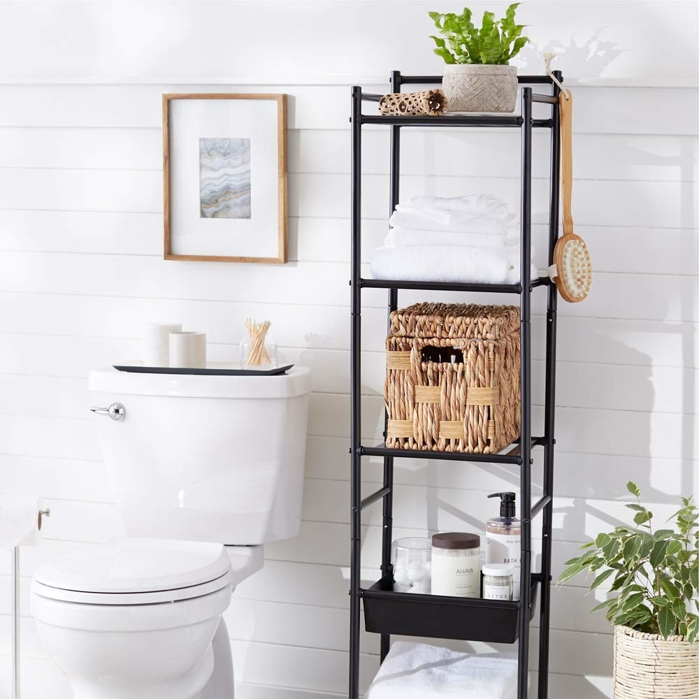 The shelving unit used to store a plant, cane basket, toiletries, and towels